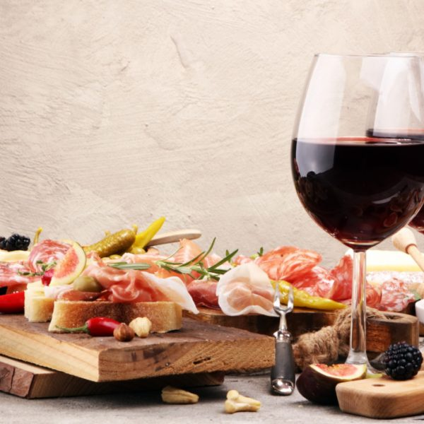 Italian antipasti wine snacks set. Cheese variety, Mediterranean olives, pickles, Prosciutto di Parma, pepper and salami
